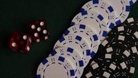 Rotating shot of poker cards and poker chips on a green felt surface - POKER 059