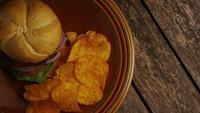 Rotierender Schuss von köstlichen Burger- und Kartoffelchips - BBQ 156