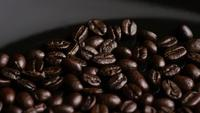 Rotating shot of delicious, roasted coffee beans on a white surface - COFFEE BEANS 015