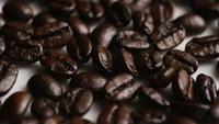 Rotating shot of delicious, roasted coffee beans on a white surface - COFFEE BEANS 043