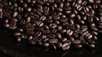 Foto giratoria de deliciosos granos de café tostados sobre una superficie blanca - CAFÉ HABAS 014