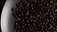 Foto giratoria de deliciosos granos de café tostados sobre una superficie blanca - CAFÉ HABAS 004