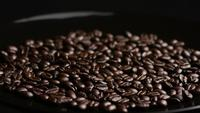 Rotating shot of delicious, roasted coffee beans on a white surface - COFFEE BEANS 021