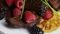 Rotating shot of a delicious smoked duck bacon dish with grilled pineapple, raspberries, blackberries, and honey - FOOD 119