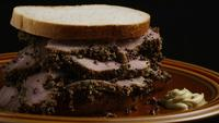 Rotating shot of delicious, premium pastrami sandwich next to a dollop of dijon mustard - FOOD 031