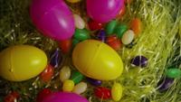 Rotating shot of Easter decorations and candy in colorful Easter grass - EASTER 005