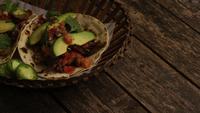 Drehender Schuss von köstlichen Tacos auf einer Holzoberfläche - BBQ 138