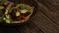 Foto giratoria de deliciosos tacos sobre una superficie de madera - BBQ 138
