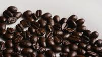 Rotating shot of delicious, roasted coffee beans on a white surface - COFFEE BEANS 041