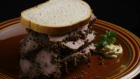 Rotating shot of delicious, premium pastrami sandwich next to a dollop of dijon mustard - FOOD 026