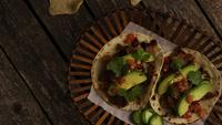 Rotating shot of delicious tacos on a wooden surface - BBQ 129