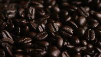 Rotating shot of delicious, roasted coffee beans on a white surface - COFFEE BEANS 071