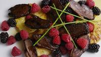 Rotating shot of a delicious smoked duck bacon dish with grilled pineapple, raspberries, blackberries, and honey - FOOD 092