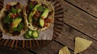 Rotating shot of delicious tacos on a wooden surface - BBQ 128