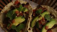 Drehender Schuss von köstlichen Tacos auf einer Holzoberfläche - BBQ 132