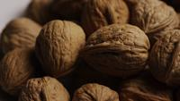 Cinematic, rotating shot of walnuts in their shells on a white surface - WALNUTS 073