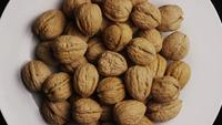 Cinematic, rotating shot of walnuts in their shells on a white surface - WALNUTS 042