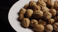 Cinematic, rotating shot of walnuts in their shells on a white surface - WALNUTS 068