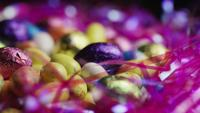 Rotating shot of colorful Easter candies on a bed of easter grass - EASTER 185