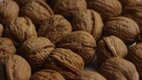 Cinematic, rotating shot of walnuts in their shells on a white surface - WALNUTS 014