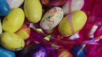 Tiro giratorio de coloridos caramelos de Pascua en un lecho de pasto de pascua - PASCUA 170
