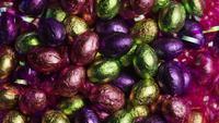 Tiro giratorio de coloridos caramelos de Pascua en un lecho de pasto de pascua - PASCUA 226