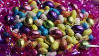 Photo en rotation de bonbons de Pâques colorés sur un lit d'herbe de Pâques - PÂQUES 172