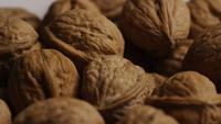 Cinematic, rotating shot of walnuts in their shells on a white surface - WALNUTS 075