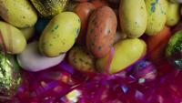 Photo en rotation de bonbons de Pâques colorés sur un lit d'herbe de Pâques - PÂQUES 169