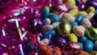 Tiro giratorio de coloridos caramelos de Pascua en un lecho de pasto de pascua - PASCUA 174