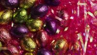 Photo en rotation de bonbons de Pâques colorés sur un lit d'herbe de Pâques - PÂQUES 202