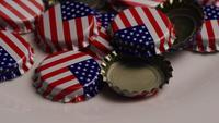 Roterande skott av flaskhattar med den amerikanska flaggan tryckt på dem - BOTTLE CAPS 034