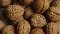 Filmische, roterende opname van walnoten in hun schelpen op een wit oppervlak - WALNOTEN 052