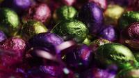 Tiro giratorio de coloridos caramelos de Pascua en un lecho de pasto de pascua - PASCUA 249