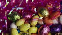Tiro giratorio de coloridos caramelos de Pascua en un lecho de pasto de pascua - PASCUA 160