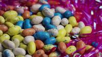 Photo en rotation de bonbons de Pâques colorés sur un lit d'herbe de Pâques - PÂQUES 126