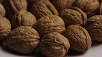 Filmische, roterende opname van walnoten in hun schaal op een wit oppervlak - WALNOTEN 015