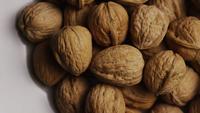 Filmische, roterende opname van walnoten in hun schaal op een wit oppervlak - WALNOTEN 051