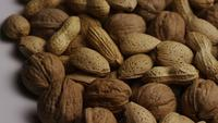 Cinematic, rotating shot of a variety of nuts on a white surface - NUTS MIXED 015