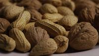 Cinematic, rotating shot of a variety of nuts on a white surface - NUTS MIXED 030