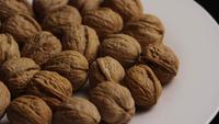 Filmische, roterende opname van walnoten in hun schaal op een wit oppervlak - WALNOTEN 012