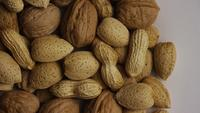 Cinematic, rotating shot of a variety of nuts on a white surface - NUTS MIXED 003