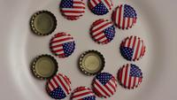 Rotating shot of bottle caps with the American flag printed on them - BOTTLE CAPS 001