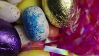 Tiro giratorio de coloridos caramelos de Pascua en un lecho de pasto de pascua - PASCUA 167