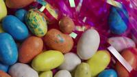 Rotating shot of colorful Easter candies on a bed of easter grass - EASTER 118