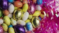 Roterend schot van kleurrijk Pasen-suikergoed op een bed van Pasen-gras - PASEN 159