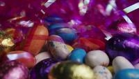Tiro giratorio de coloridos caramelos de Pascua en un lecho de pasto de pascua - PASCUA 177