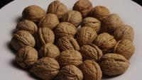 Filmische, roterende opname van walnoten in hun schaal op een wit oppervlak - WALNOTEN 011