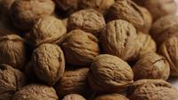 Filmische, roterende opname van walnoten in hun schaal op een wit oppervlak - WALNOTEN 072