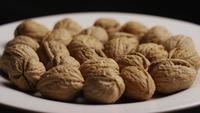 Filmische, roterende opname van walnoten in hun schaal op een wit oppervlak - WALNOTEN 027
